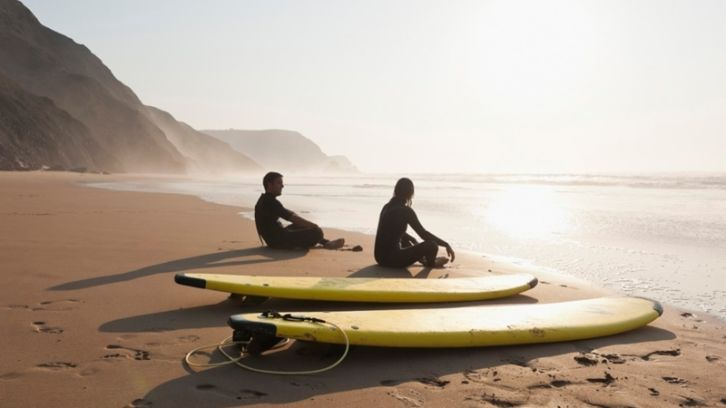 surfers sitting on beach facing the ocean