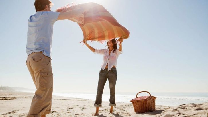 couple spreading picnic blanket on beach