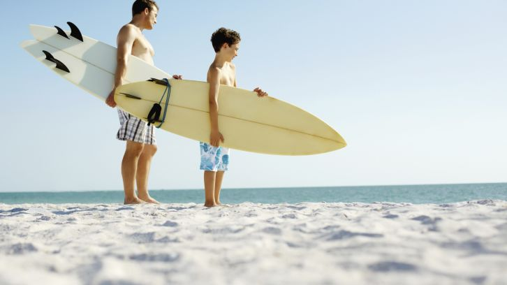 father and son holding surfboards on beach