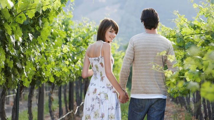 couple waling through vineyard