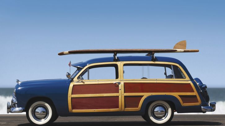 vintage car with surfboard on hood