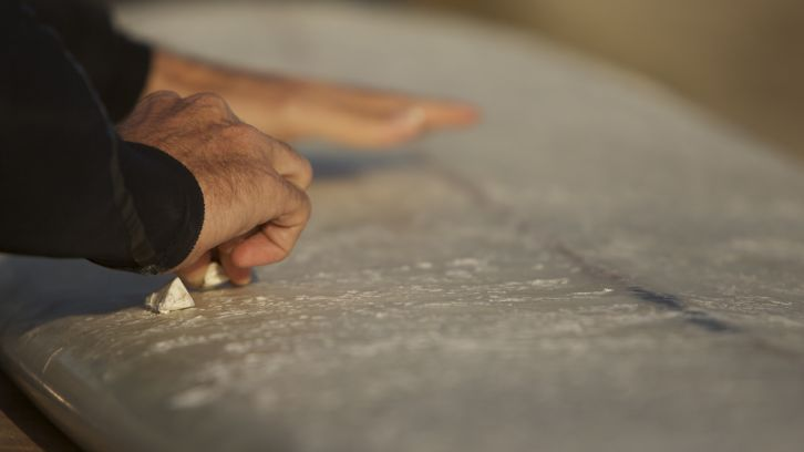 surfer chalking surf board