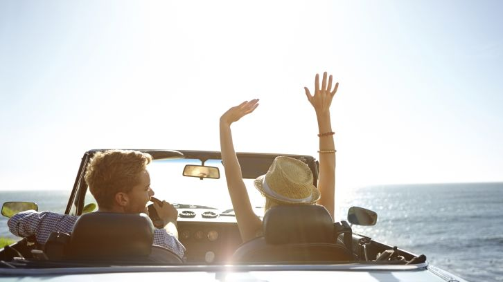 couple in convertible driving along the ocean