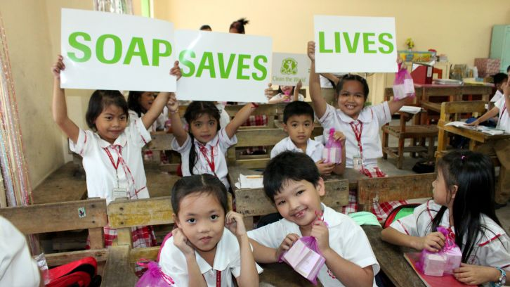 children in school holding signs that read: soap saves lives