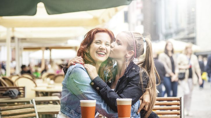 two women friends embracing over coffee