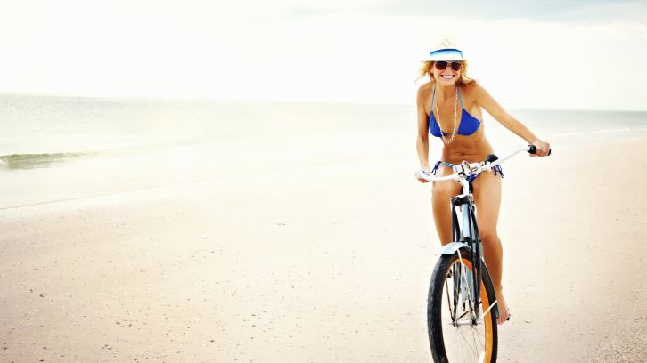 woman in bikini riding bike on beach