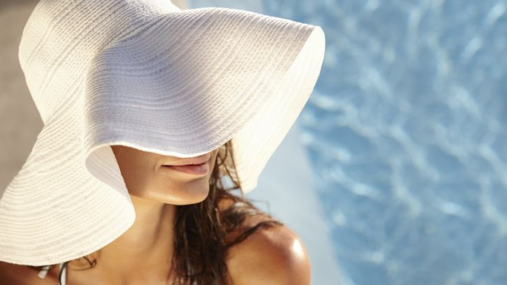 woman in sunhat by pool