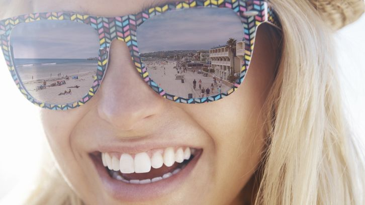 Smiling woman in sunglasses, beach and boardwalk reflected in her lenses