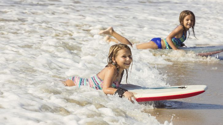 two little girls body boarding in ocean