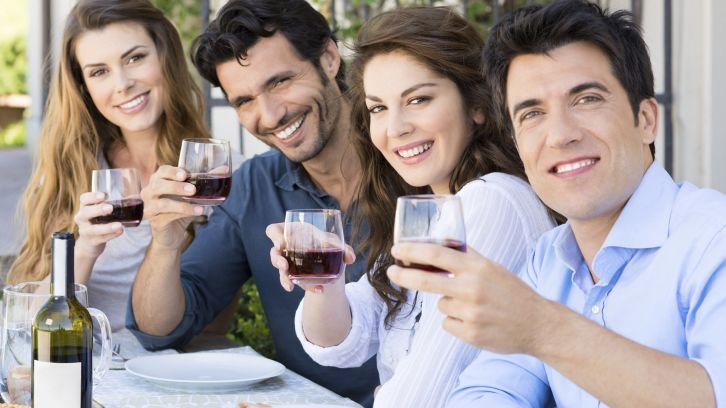friends at lunch holding up wine glasses