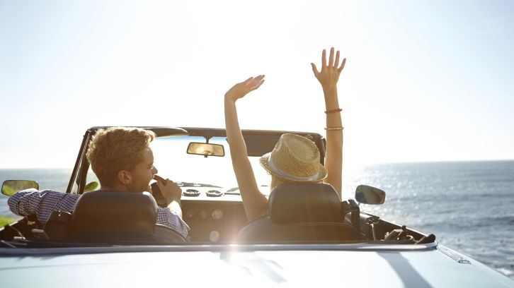 couple in convertible driving along ocean