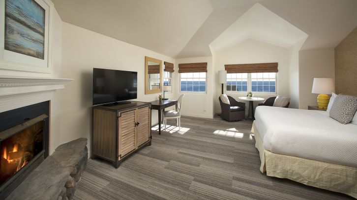 hotel suite bedroom with fireplace, tv, oceanview