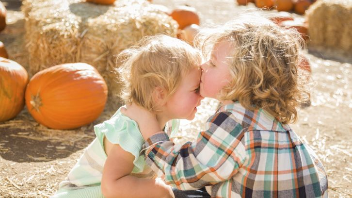 small siblings in pumpkin patch