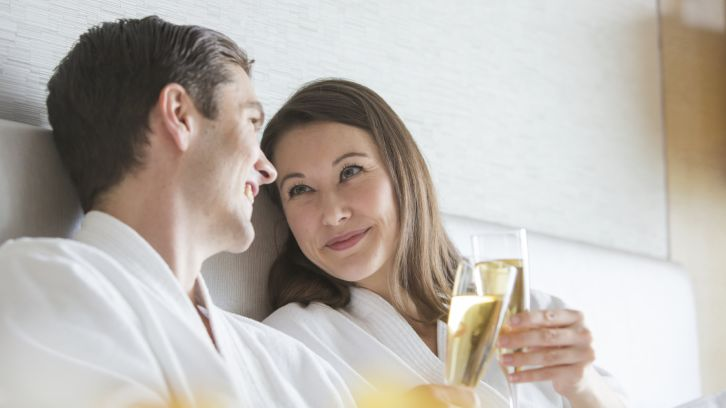 couple having mimosas in bed