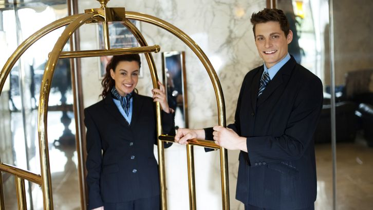 hotel concierges standing by luggage cart