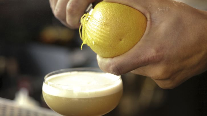 bartender peeling lemon garnish for cocktail