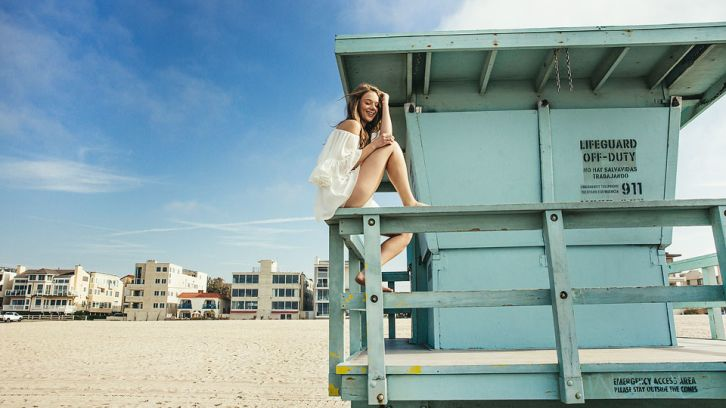 woman sitting on lifeguard tower railing