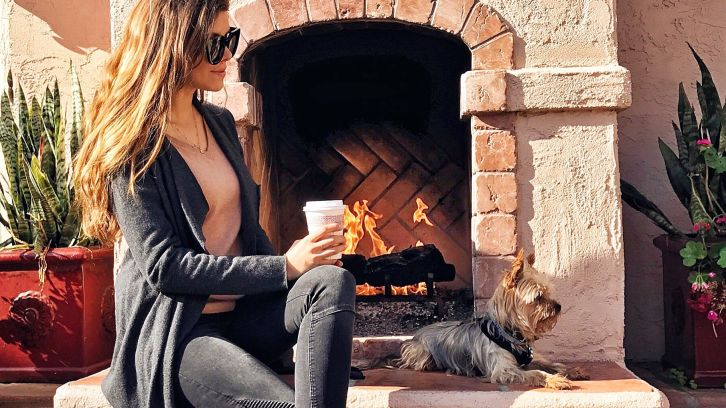 woman having coffe by outdoor fireplace