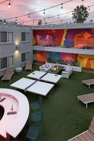 hotel courtyard with wall murals, bar, deck chairs, ping pong tables