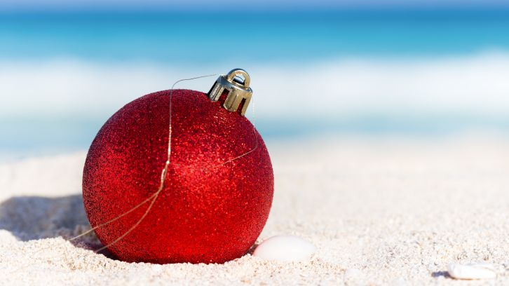 red Christmas ornament on sand