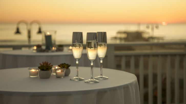 champagne in glasses on outdoor table, sunset and ocean backdrop