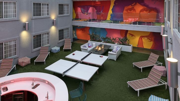 outdoor patio with jim morrison murals, deck chairs, bar, ping pong tables