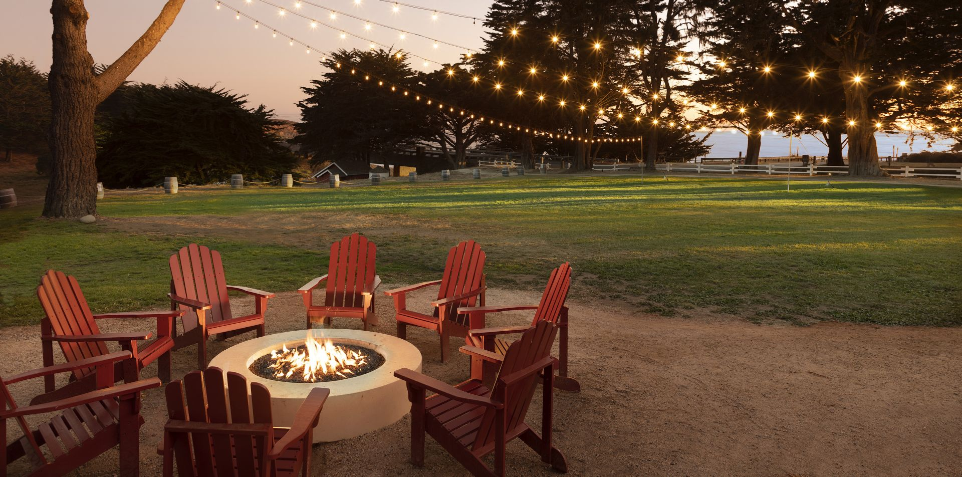 outdoor fire pit with red chairs and lights