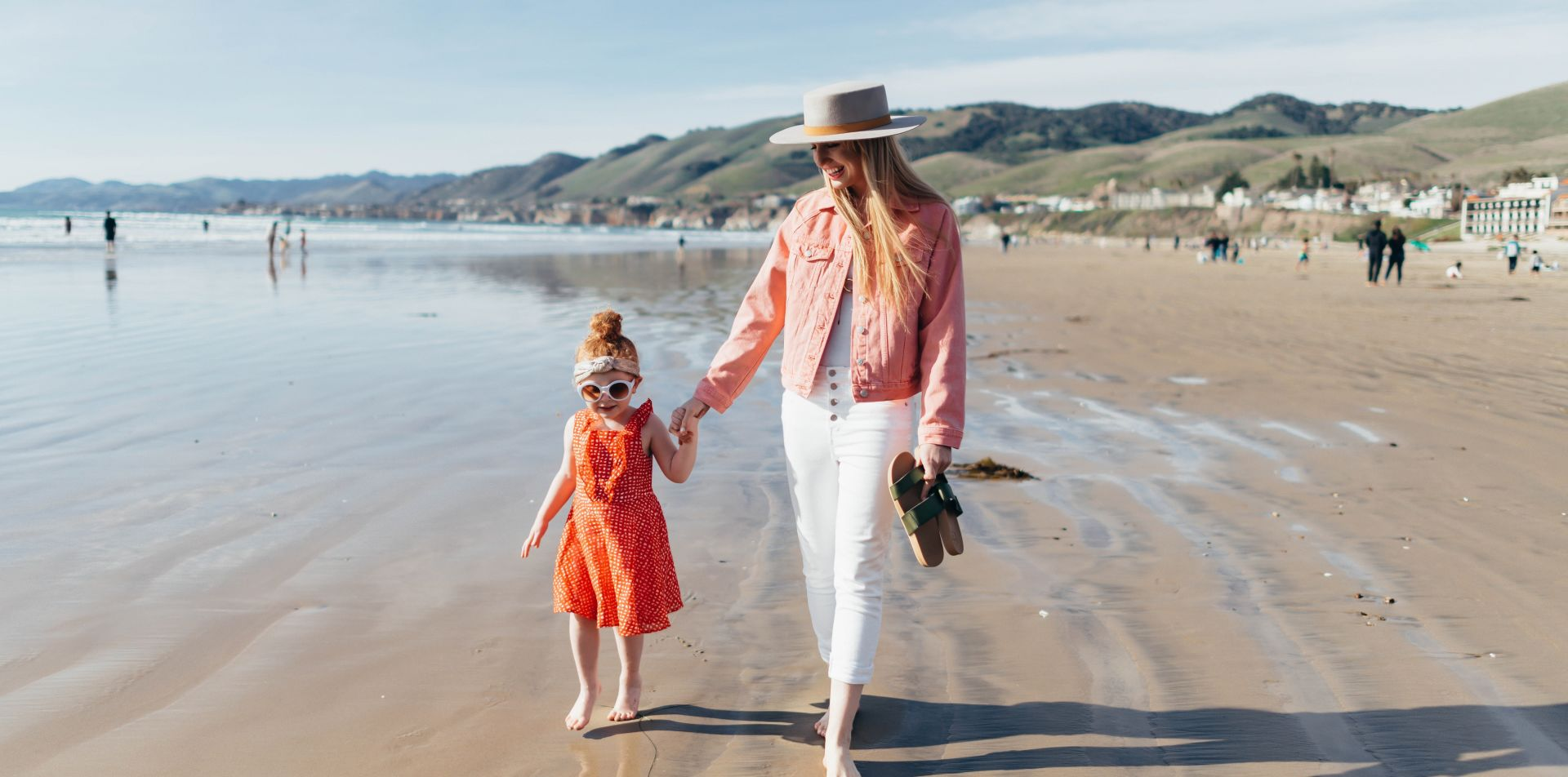 A Mom & Daughter Walking On A Beach